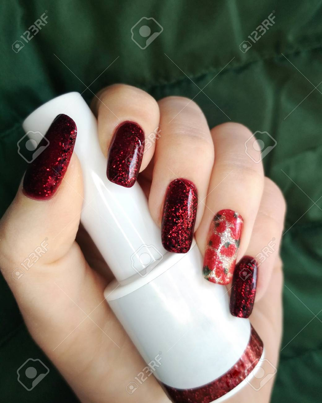 Woman hand finger black and red flower manicure gel nail polish..