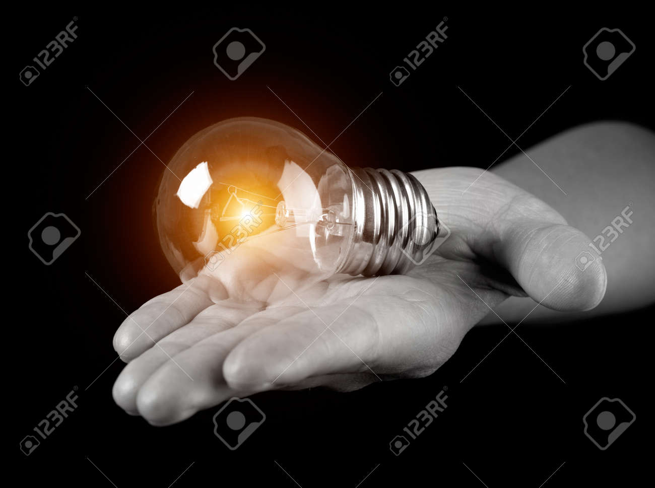 Hand holding light bulb isolated on black Stock Photo - 13698516