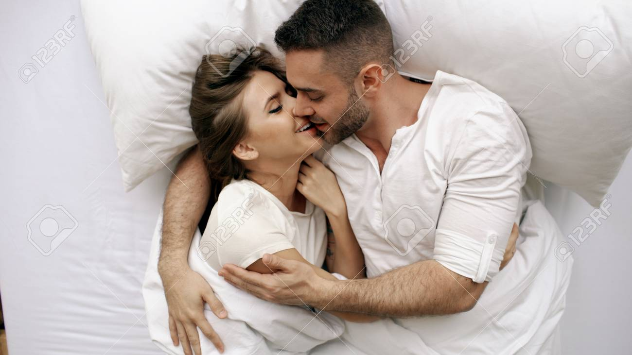 Young Beautiful And Loving Couple Kiss Hug Into Bed While