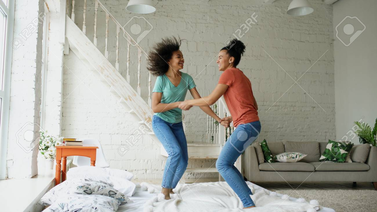 Mixed race young beautiful girls dancing on a bed together having..