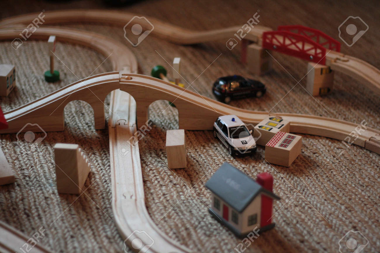 Wooden race cars with light cars and buildings on a carpet in