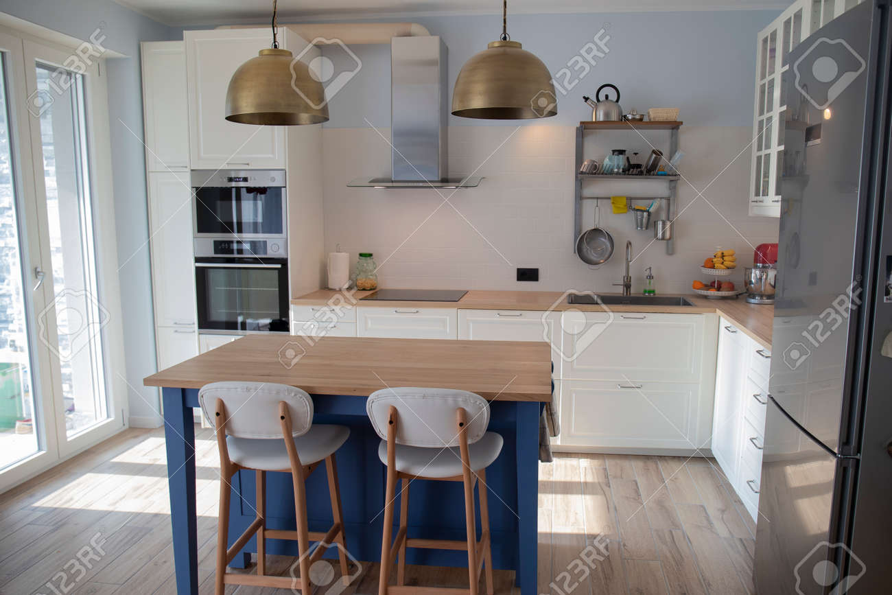 White Bright Kitchen With Blue Island And Double Brass Pendant Stock Photo Picture And Royalty Free Image Image 143721911