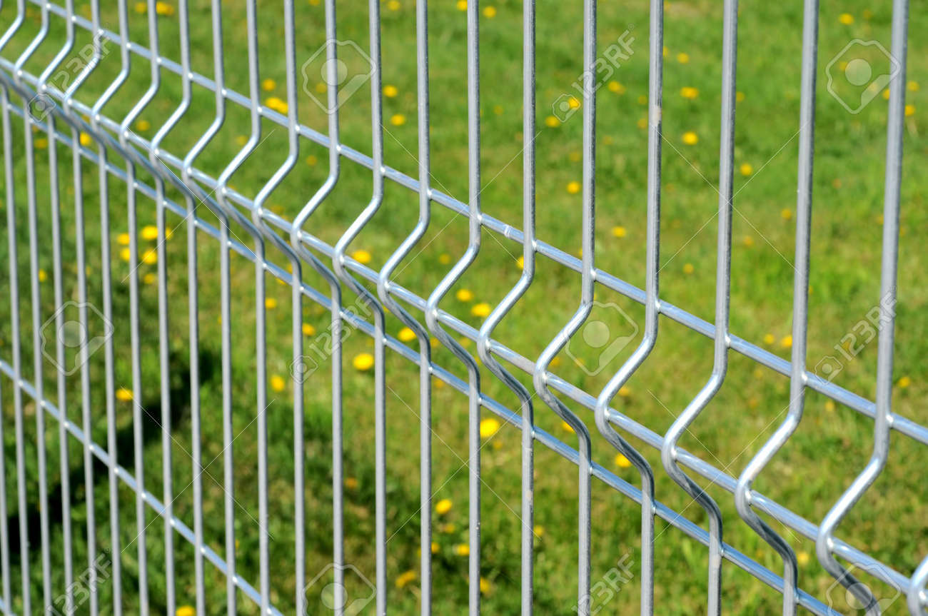 chromium metal fence with green grass in background selective focus stock photo