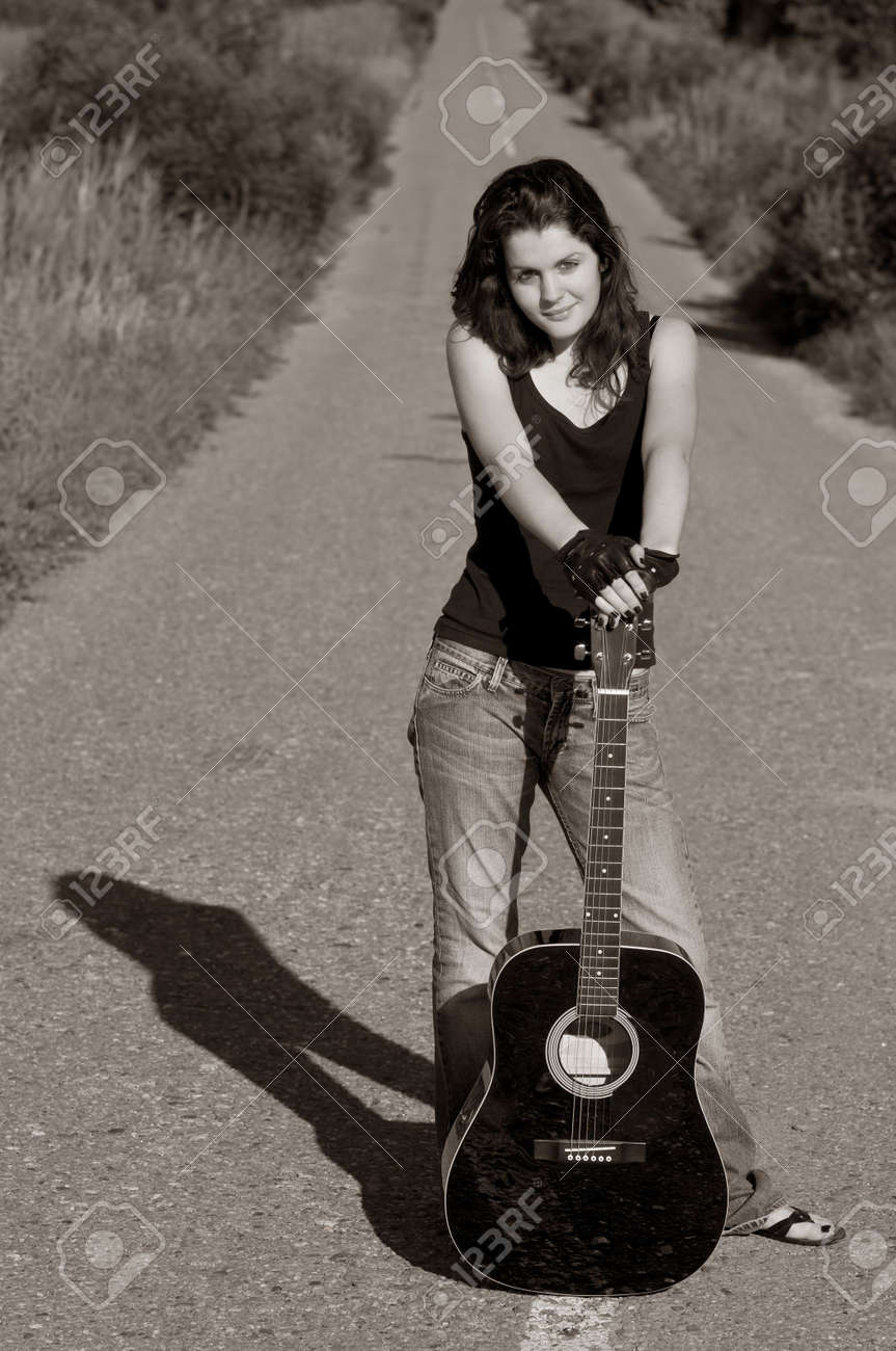 teenage girl with acoustic guitar on the road stock photo picture