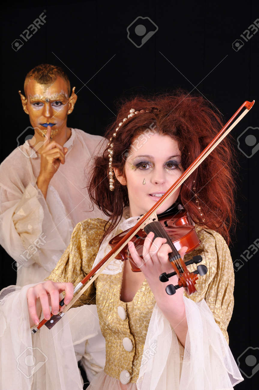 Young man and girl playing violin with faces artistic painted Stock Photo - 6165397