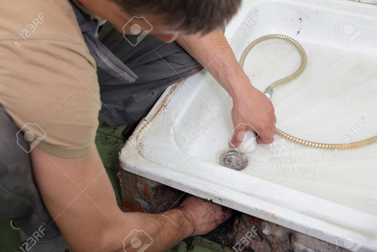 Plumber checking  drain in bathroom with shower Stock Photo - 10555108