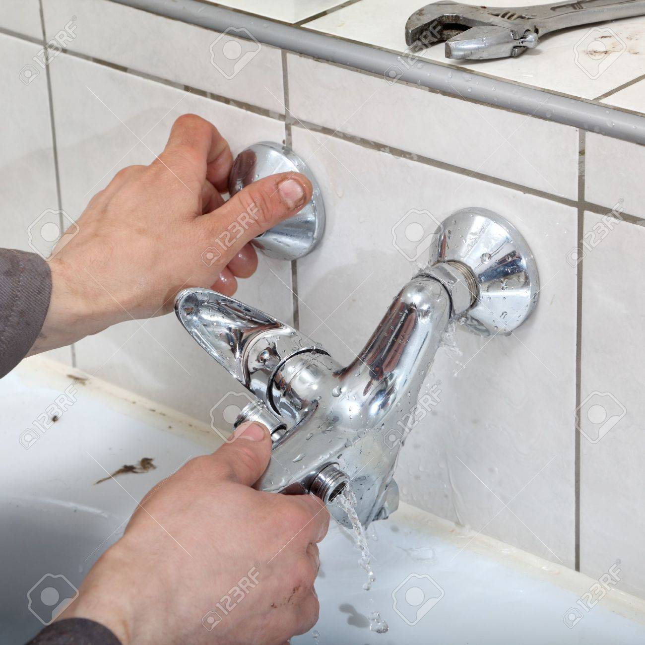 Plumber Hands Fixing Water Tap With Leaking Water Stock Photo ...