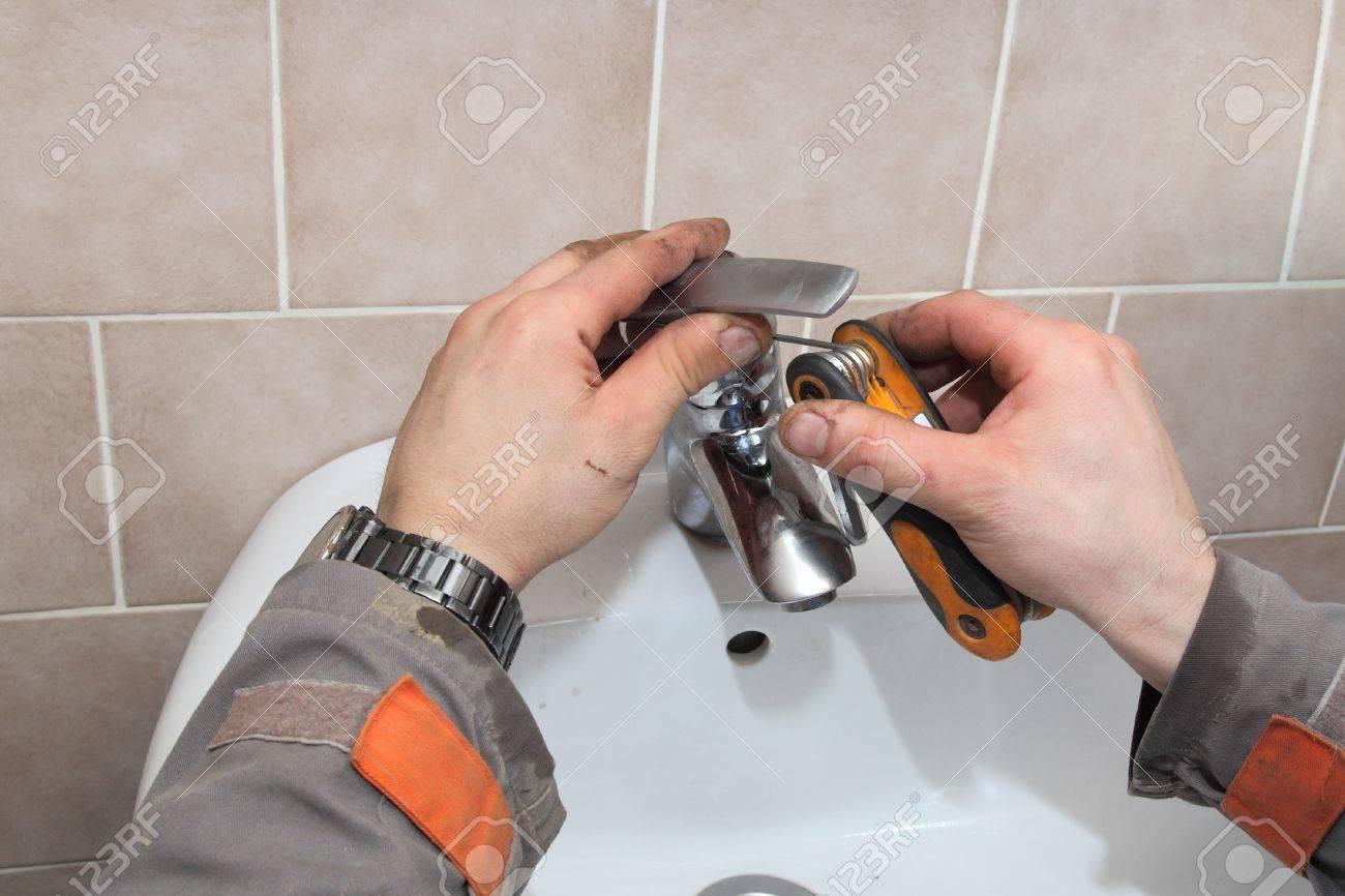 Plumber Fixing Water Tap In A Bathroom Using Allen Key Stock Photo ...