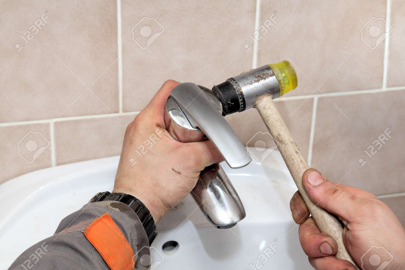 Plumber Fixing Water Tap In A Bathroom Using Hammer Stock Photo ...