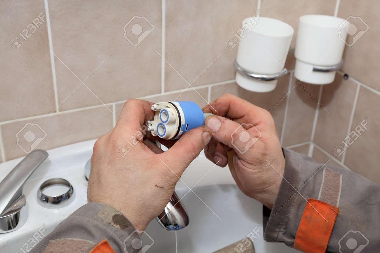 Plumber Fixing Water Tap Ceramic Cartridge Valve In A Bathroom Stock ...