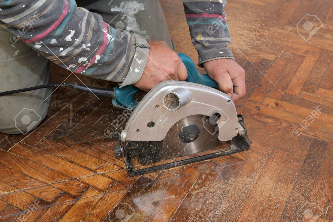 Worker cut old parquet floor with electric saw Stock Photo - 23174570