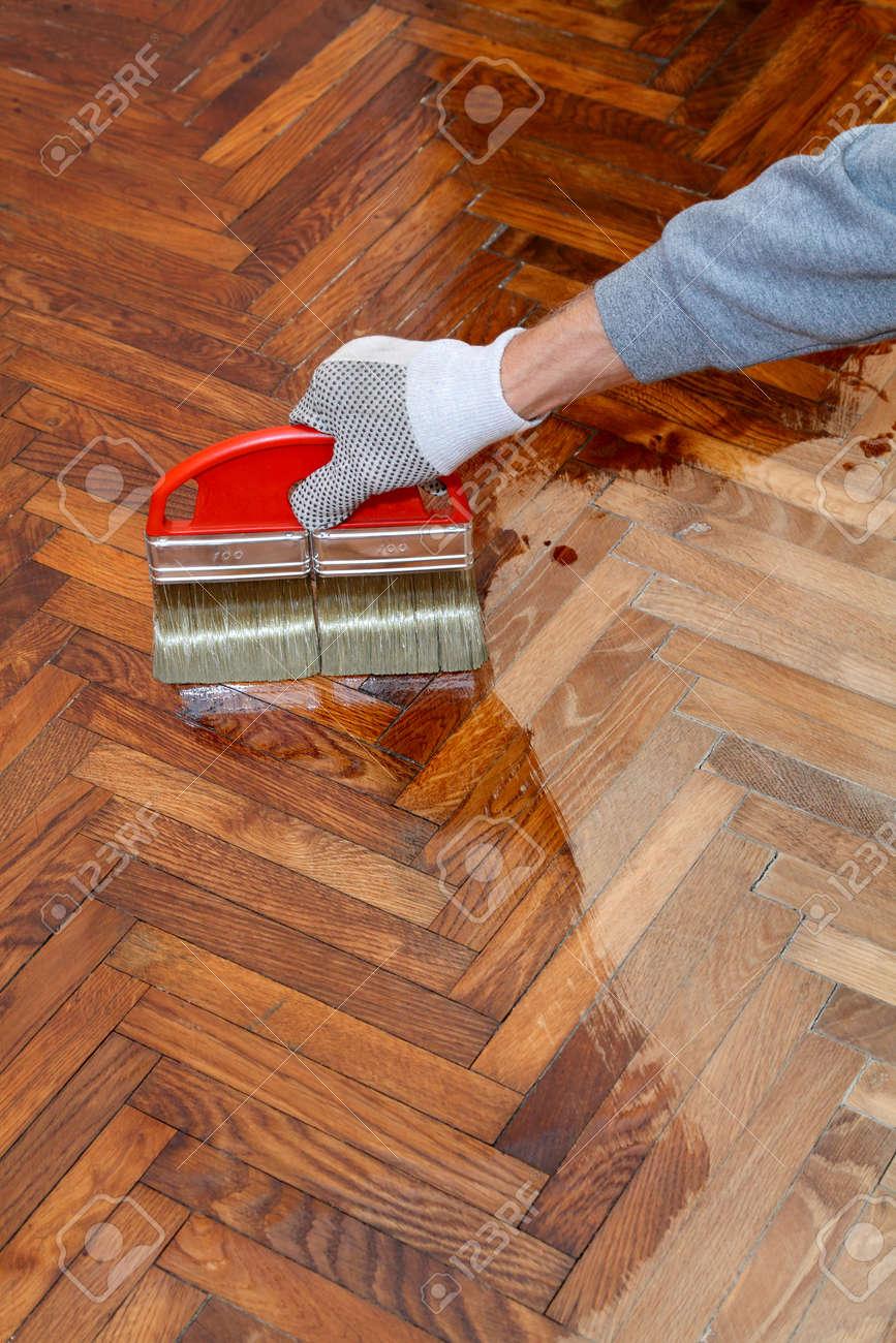 Varnishing Of Oak Parquet Floor Workers Hand In Glove And Brush