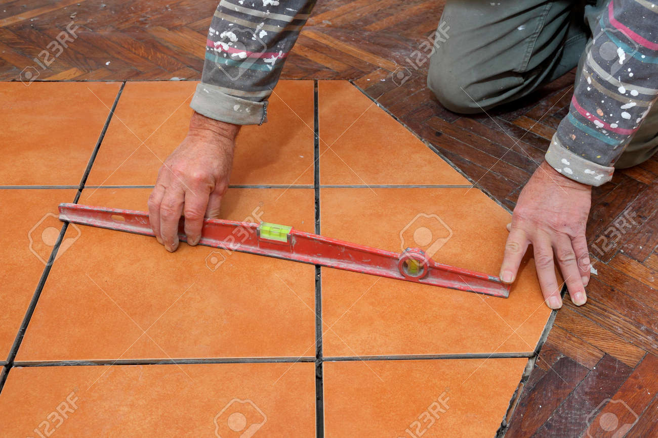 Home Renovation, Worker Levelling Tiles With Level Tool Stock Photo ...