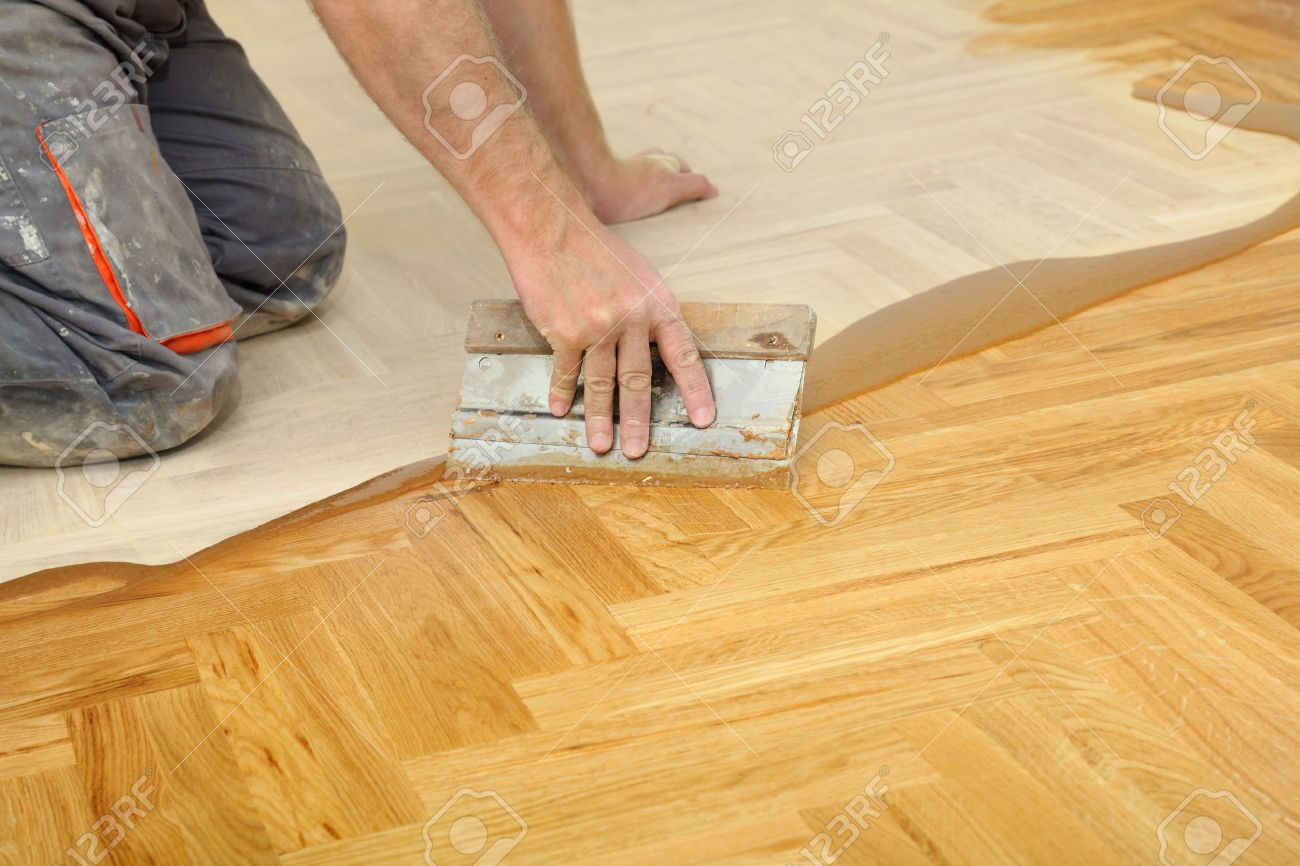 Varnishing Of Oak Parquet Floor Workers Hand And Tool Stock Photo