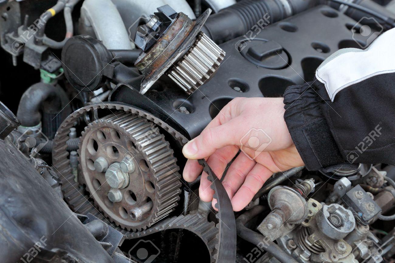 Car mechanic replacing timing belt at camshaft of modern engine - 26591261