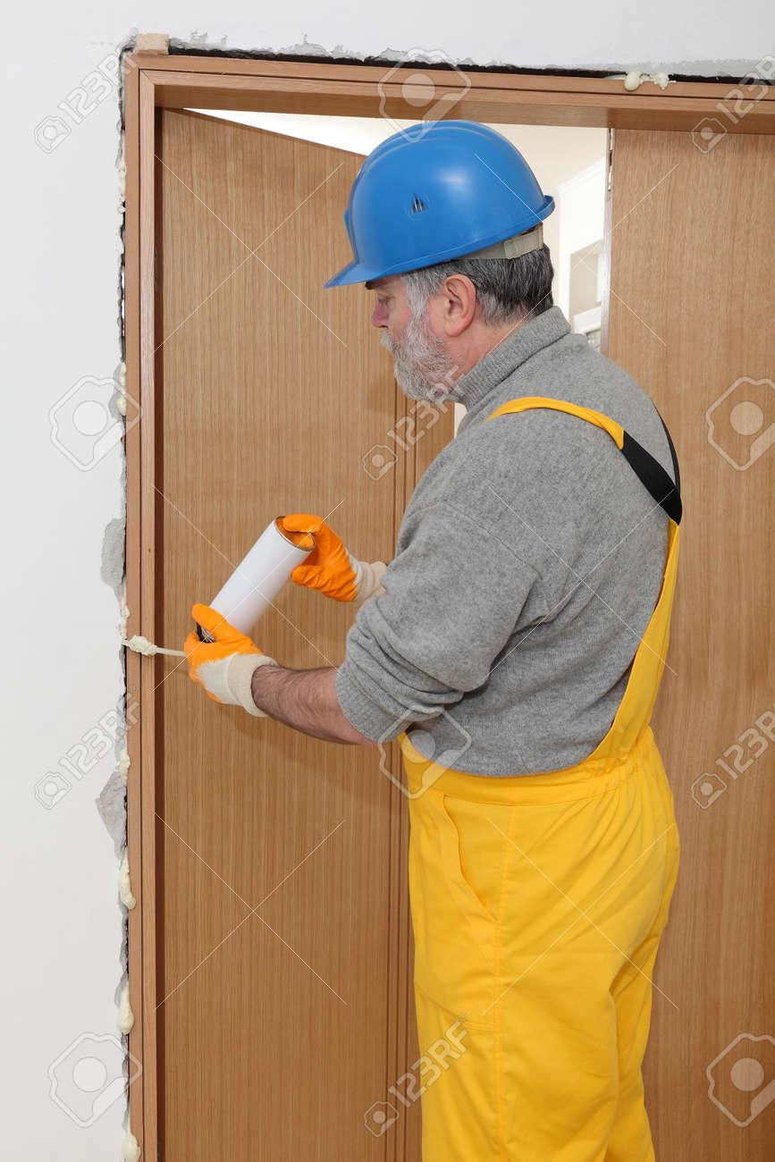 Stock Photo - Worker install door using polyurethane foam to fix it at wall & Worker Install Door Using Polyurethane Foam To Fix It At Wall Stock ...