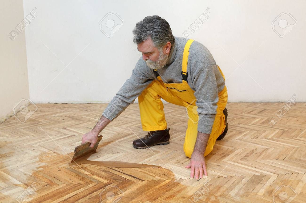 Varnishing Of Oak Parquet Floor Mature Adult Worker Using Tool