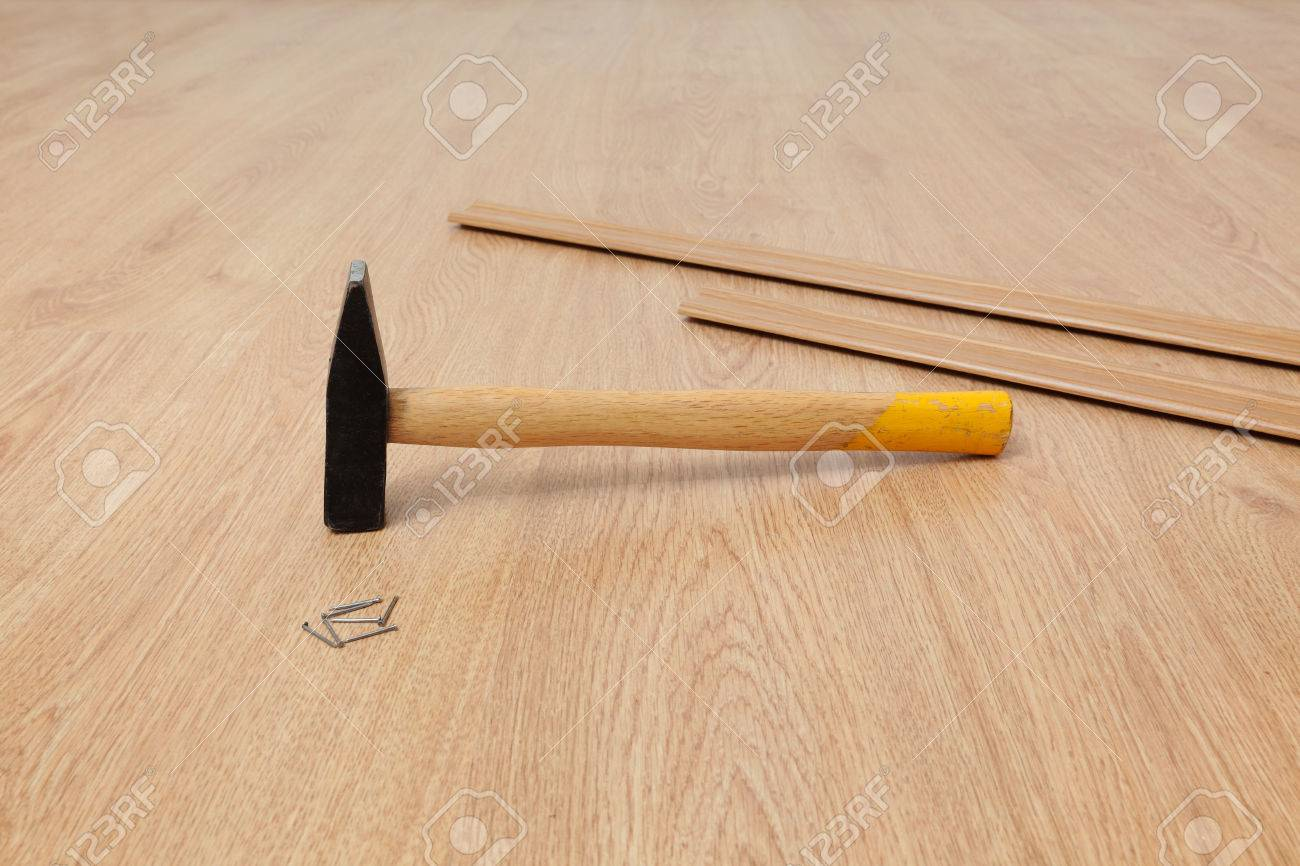 closeup of hammer nails and batten for laminate floor floating closeup of hammer nails and batten for laminate floor floating wood tile stock photo