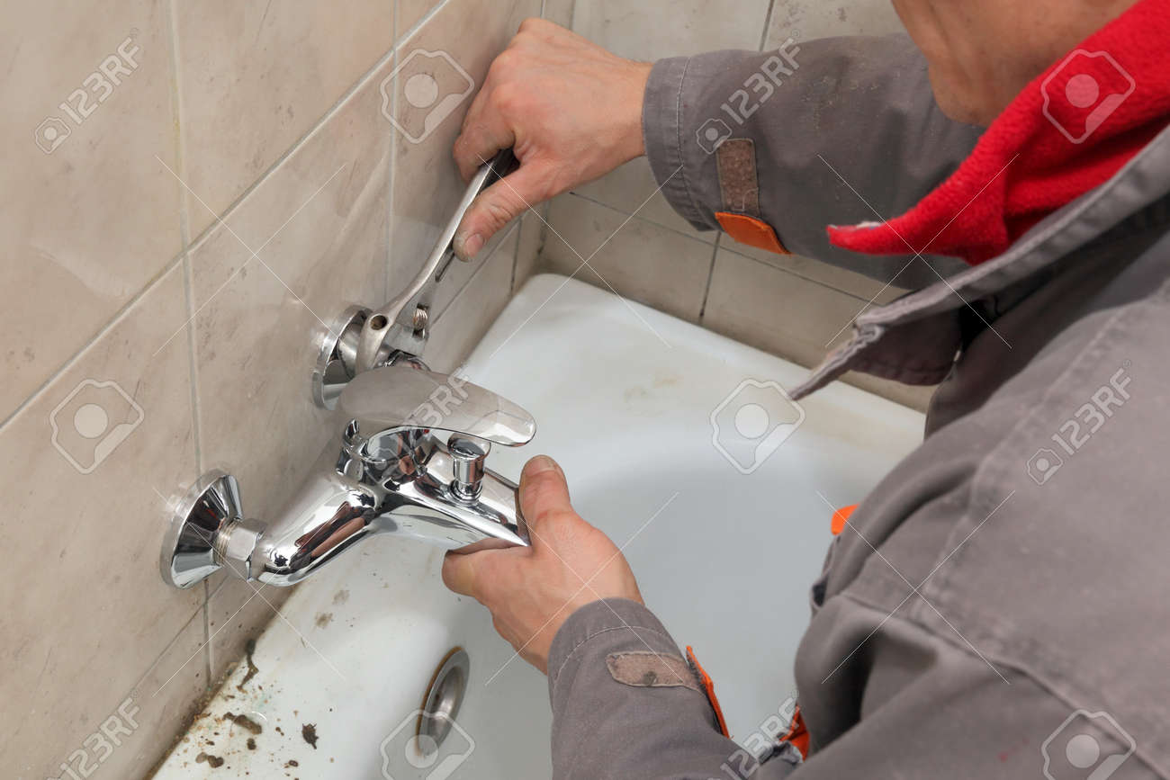 Plumber Fixing Water Tap In A Bathroom Using Spanner Stock Photo ...