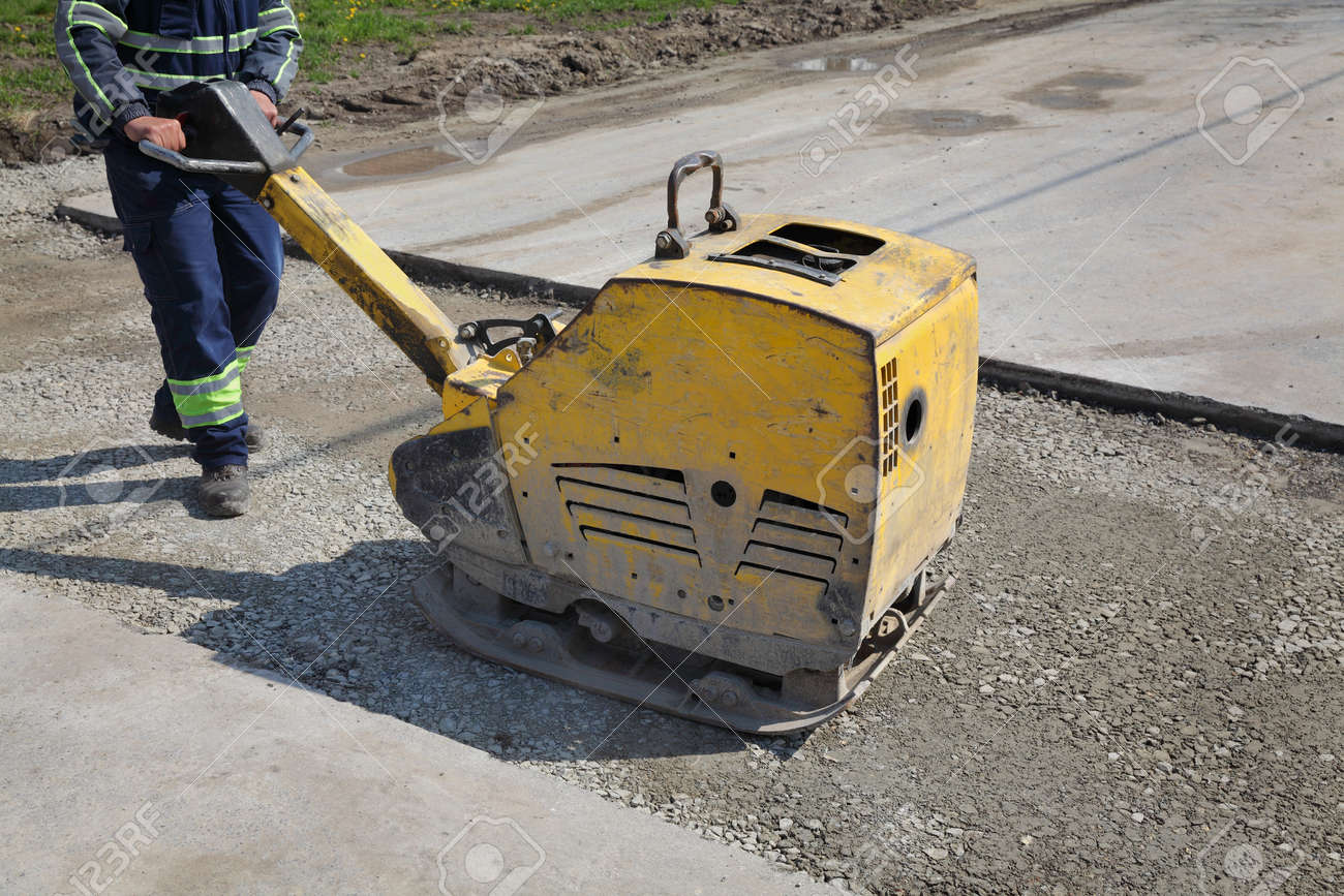 worker use vibratory plate compactor compacting gravel at road