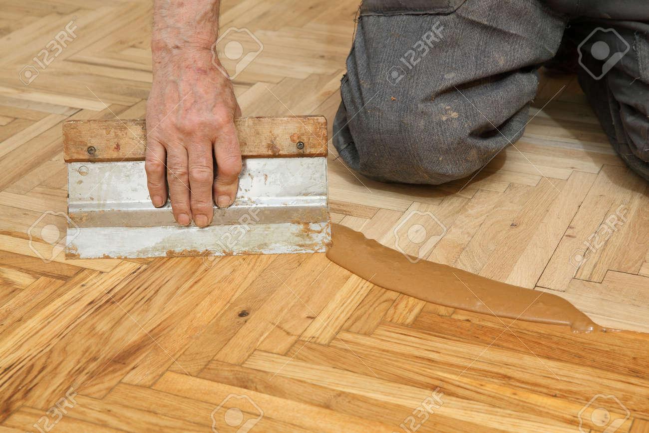 Varnishing Of Oak Parquet Floor Senior Workers Hand And Tool