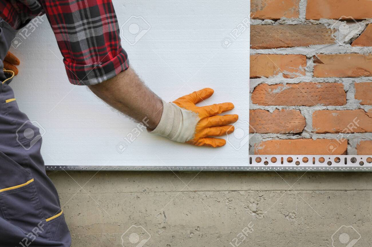 Worker placing foam, polystyrene thermal insulation to brick wall, house renovation - 126577545
