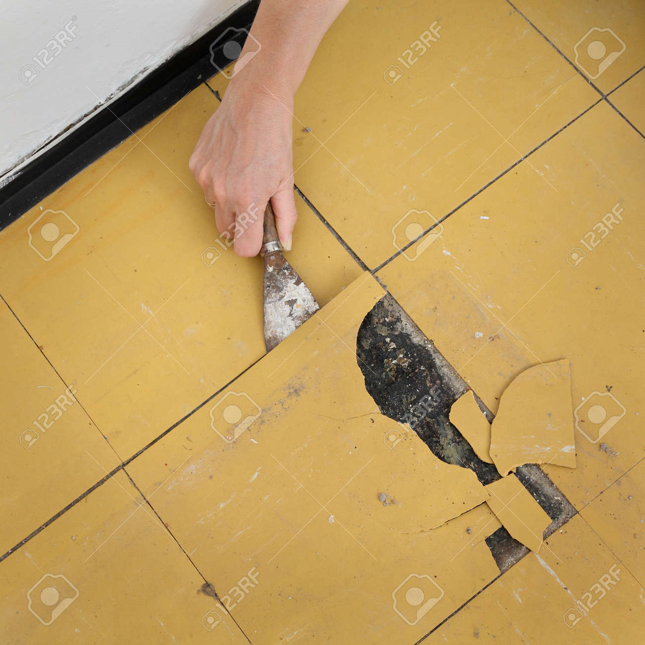 Worker Removing Old Vinyl Tiles From Kitchen Floor Using Spatula