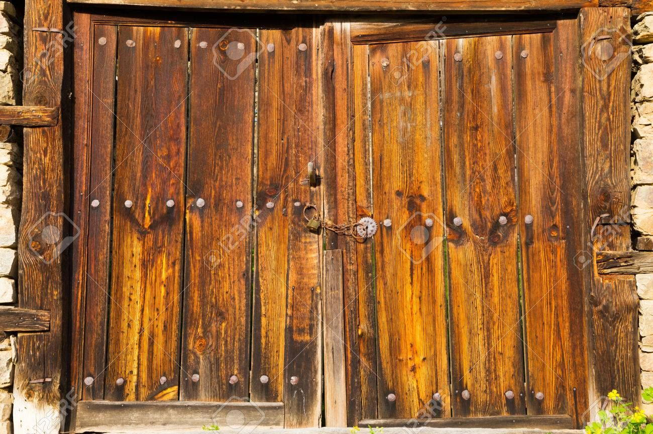 Old Double Rustic Wooden Barn Doors In Stone Walls Made From Rows Of Nails  And Timber