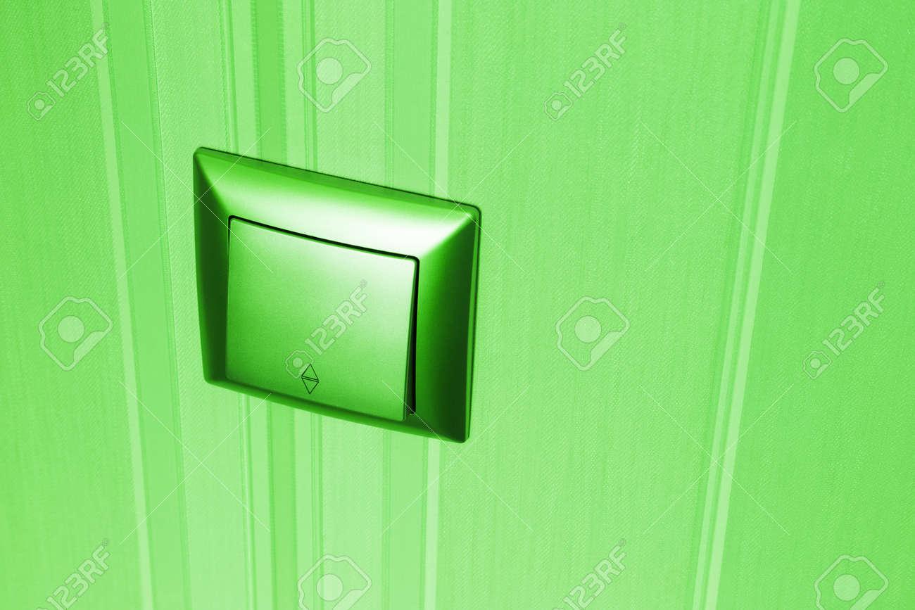 Grüner Elektrischer Lichtschalter Des Plastiks Brachte An Einer Wand An,  Die Mit Gestreifter Grüner Tapete