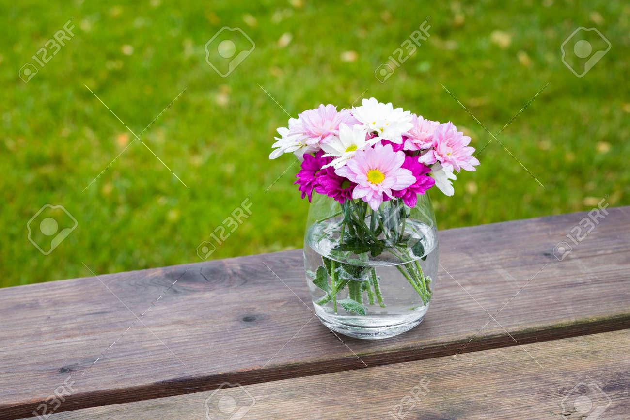 Fleurs d\'été rose coloré dans un vase de verre à l\'extérieur sur une table  de jardin en bois rustique avec espace copie sur l\'herbe verte