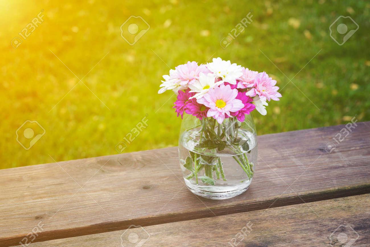 Fleurs d & # 39 ; été rose colorées dans un vase en verre assis sur une  table en bois rustique jardin avec espace copie sur l & # 39 ; herbe verte  ...