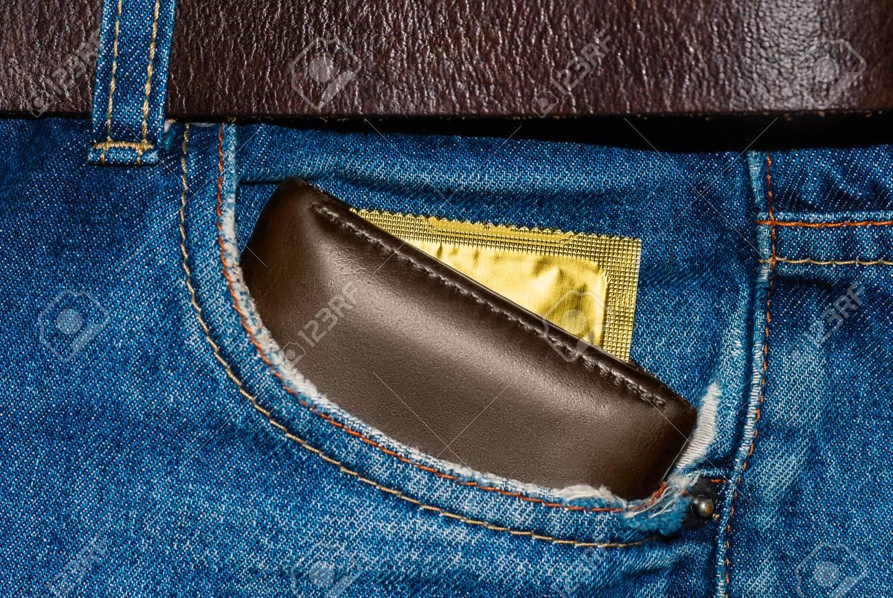 7136d09f3 Billetera en un bolsillo de jeans azul con un condón de oro. Foto de archivo