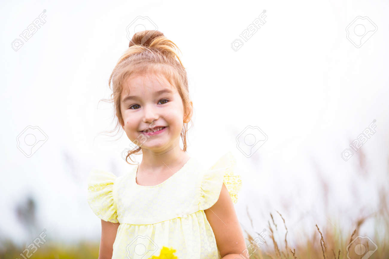 Portrait of a cute girl in field with a wild flower. Childhood, holidays in the country, freedom and carelessness. Summer time. International Children Day. Mosquito repellent, cottage core. Copy space - 169434707