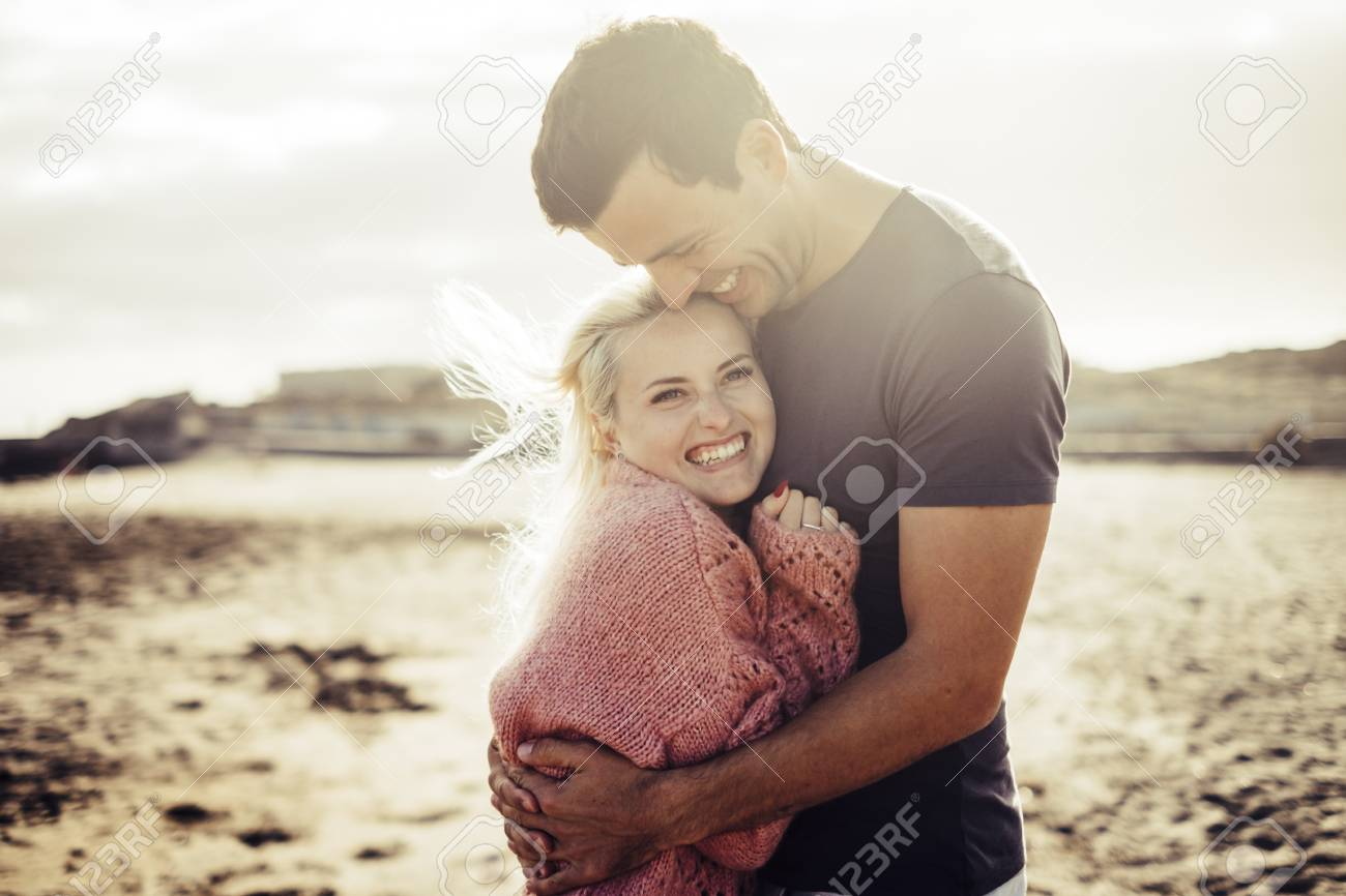 Wonderful young couple hug and enjoy life together with natural outdoor laisure activity lifestyle at the beach during the summer and the sunset in