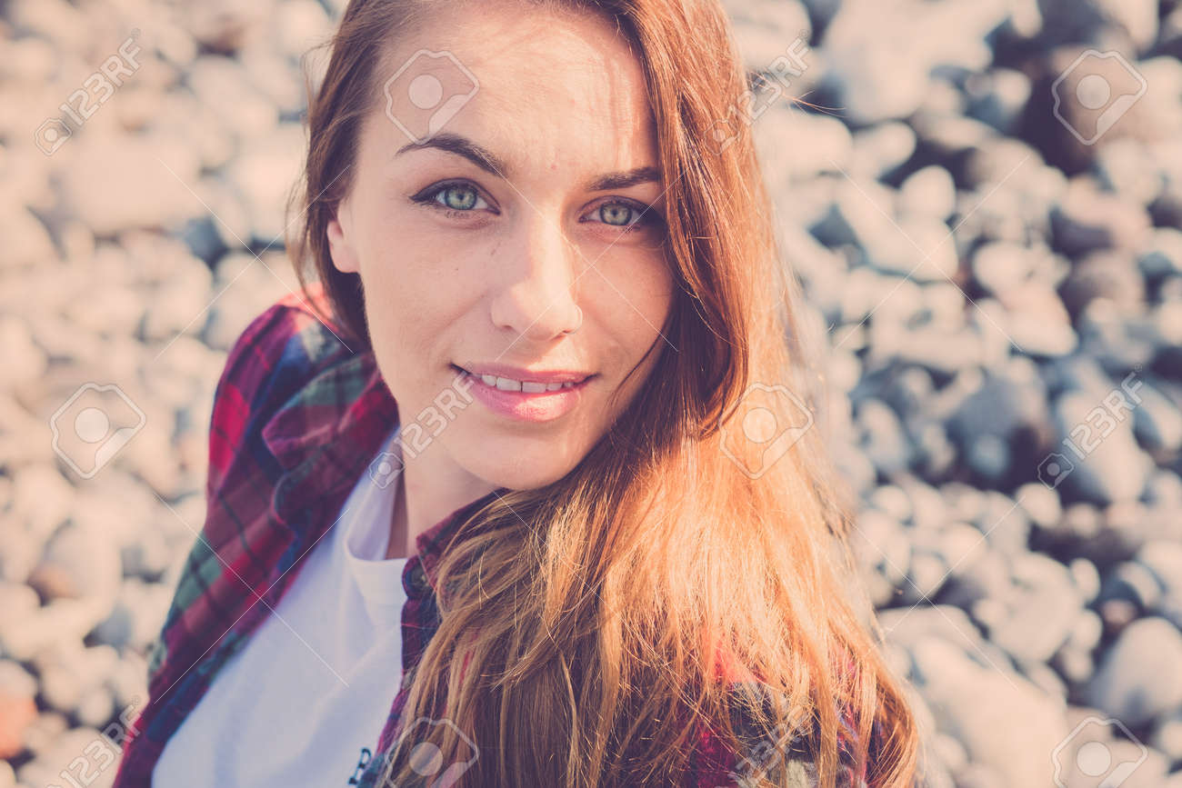 Attractive caucasian young woman smile and look at the camera - sunlight and blue eyes - vintage filter - defocused pattern background - 121843318