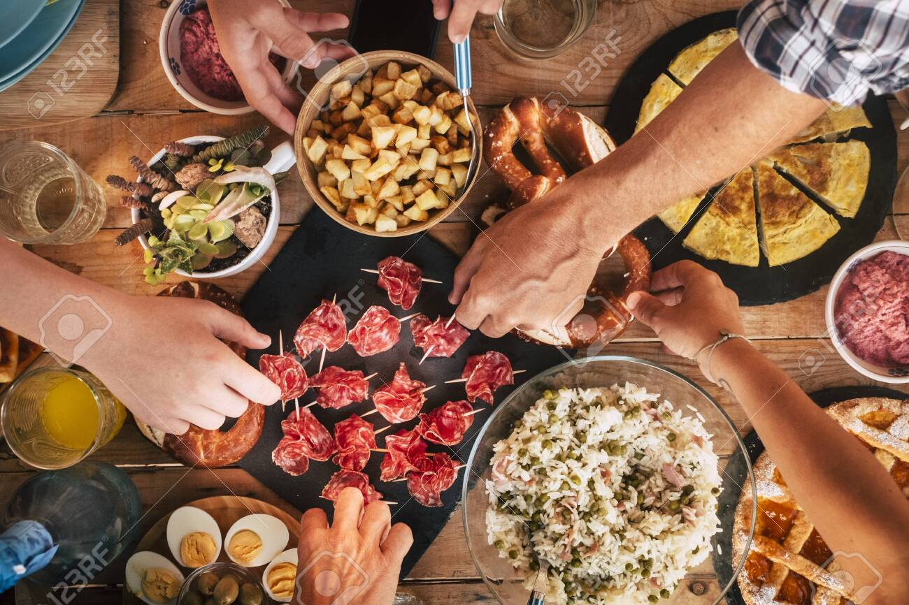 People enjoying friends concept - Tasty lunch or dinner concept with top view table full of delicious food and friends people taking and serving to eat together - coloured and wooden background - 132077530