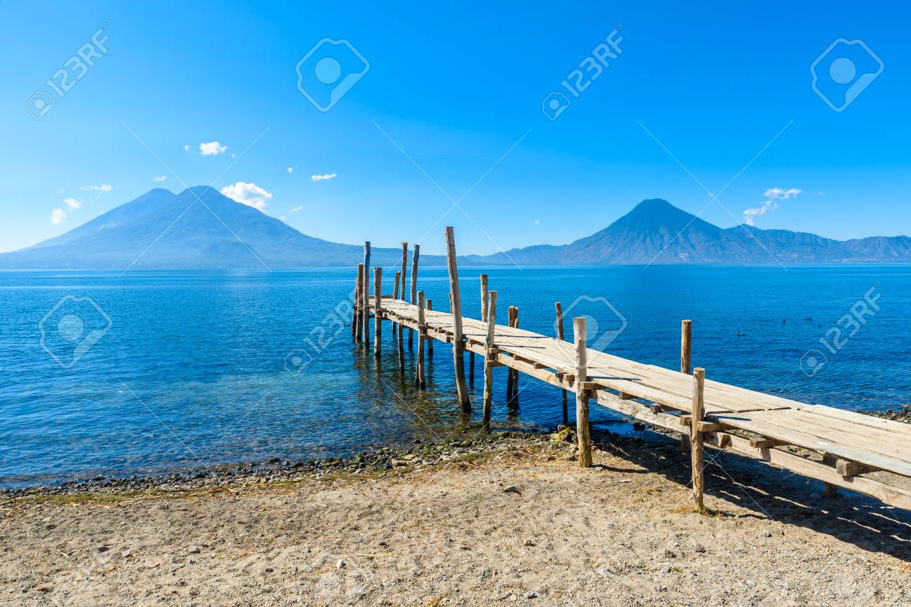 Wooden pier at Lake Atitlan on the beach in Panajachel, Guatemala. With beautiful landscape scenery of volcanoes Toliman, Atitlan and San Pedro in the background. - 91169879