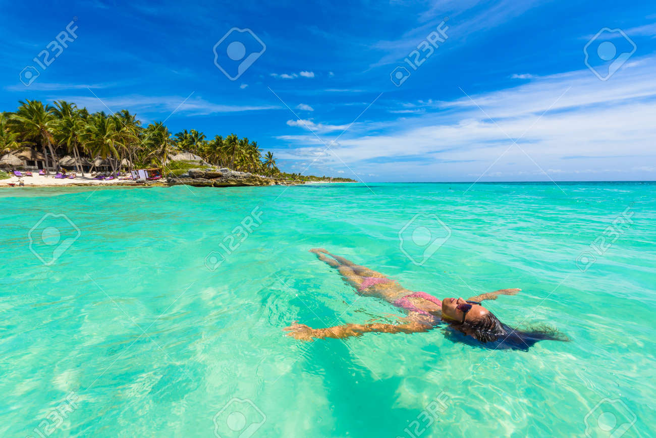 Attractive young woman relaxing in turquoise waters of Caribbean Sea in front of paradise beach in Tulum, close to Cancun, Riviera Maya, Mexico - 97631025