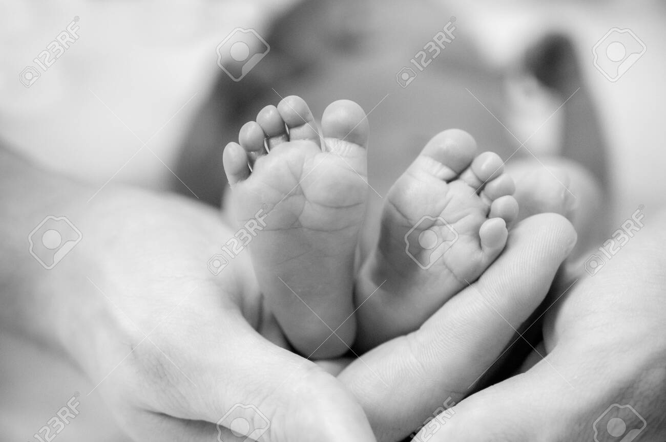 Feet of a newborn baby in the hands of parents. Happy family moment and concept. - 142946236