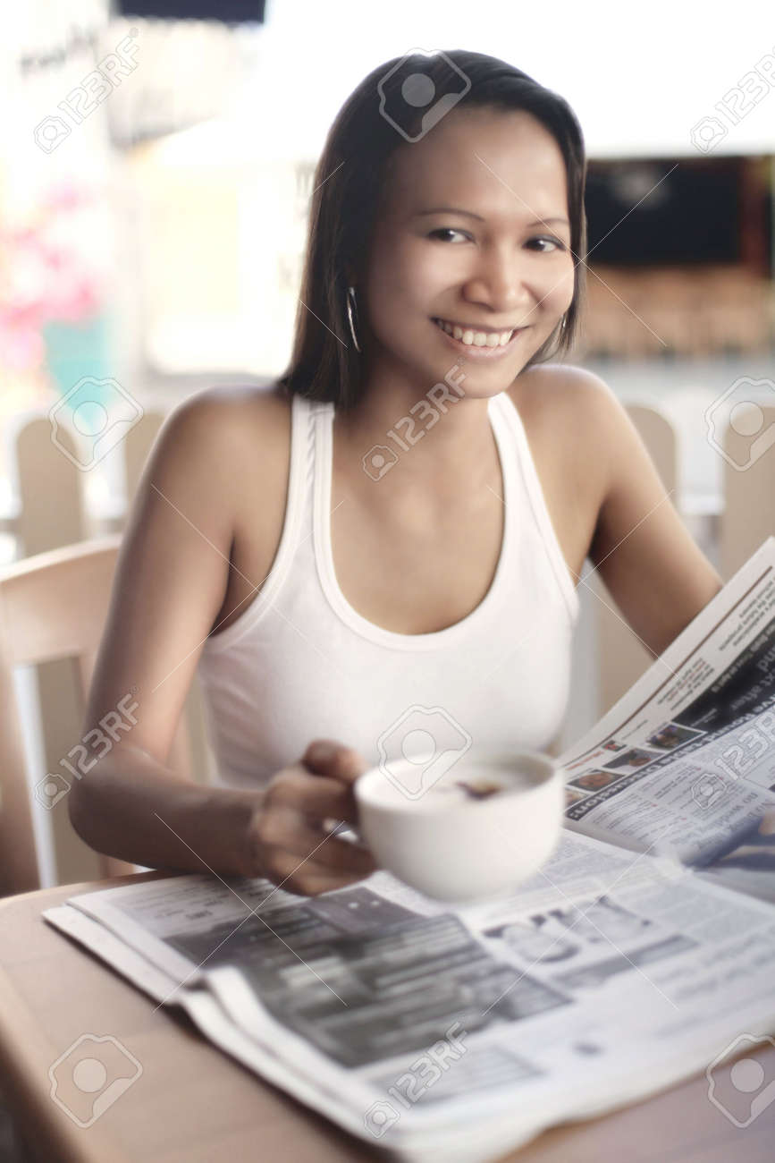 Young Asian Female Reading a Newspaper Over Coffee Stock Photo - 4868274