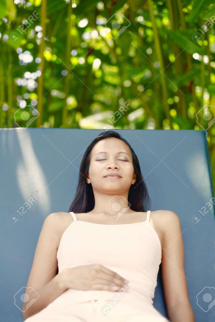 Peachy Young Asian Female Relaxing On A Reclining Chair Creativecarmelina Interior Chair Design Creativecarmelinacom