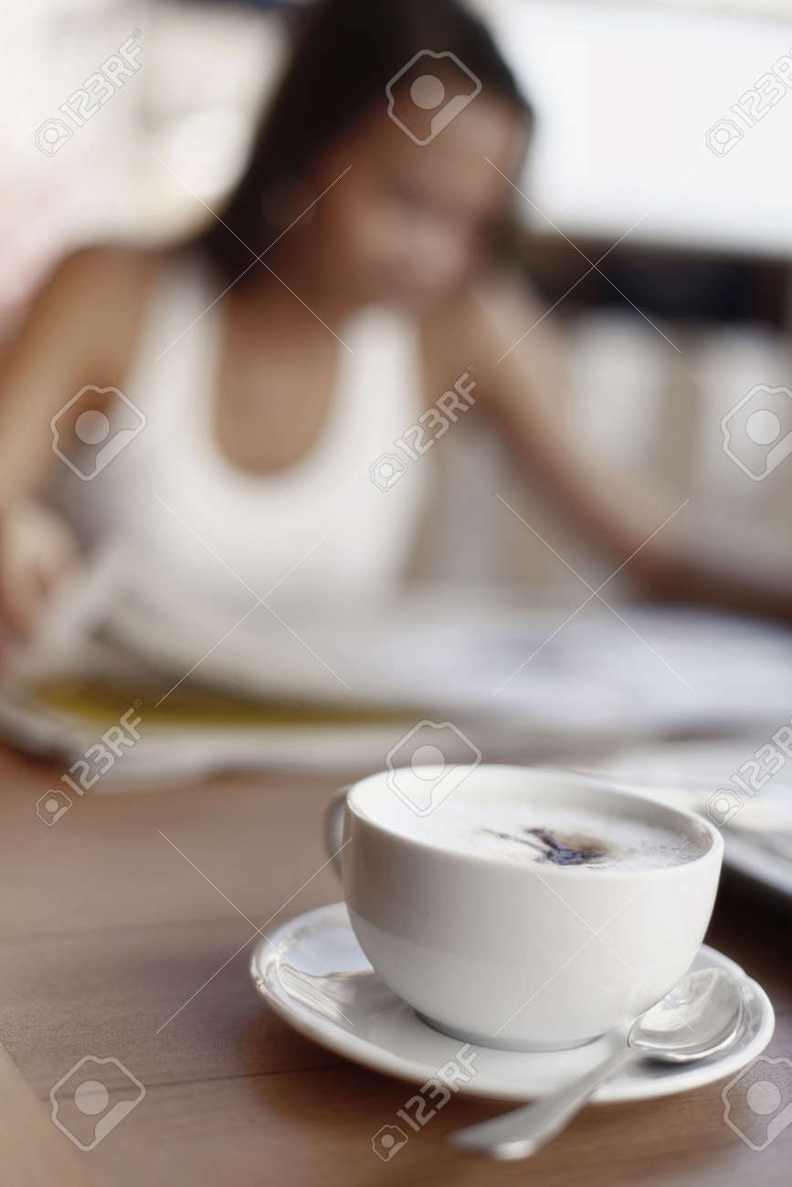 Cup of Cappuccino Coffee with Asian Female in Background Stock Photo - 4861390