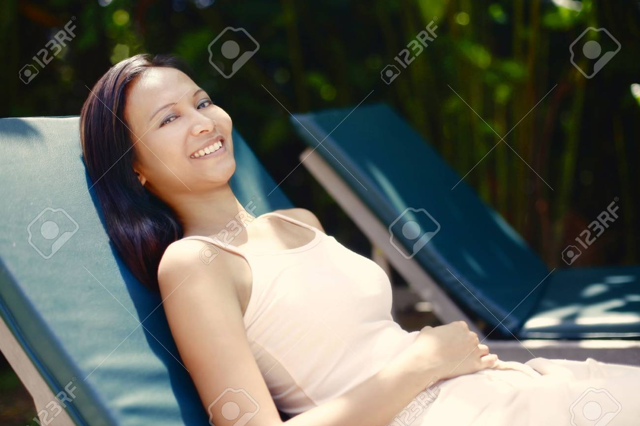 Excellent Young Asian Female Relaxing On A Reclining Chair Creativecarmelina Interior Chair Design Creativecarmelinacom