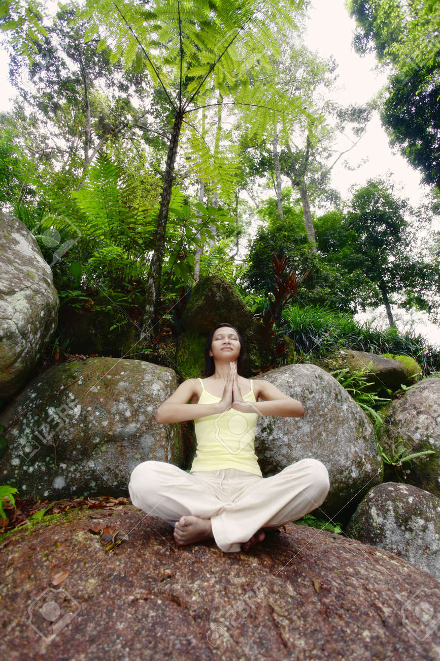Young Asian Female Sitting on a Rock and Meditating Stock Photo - 4861398