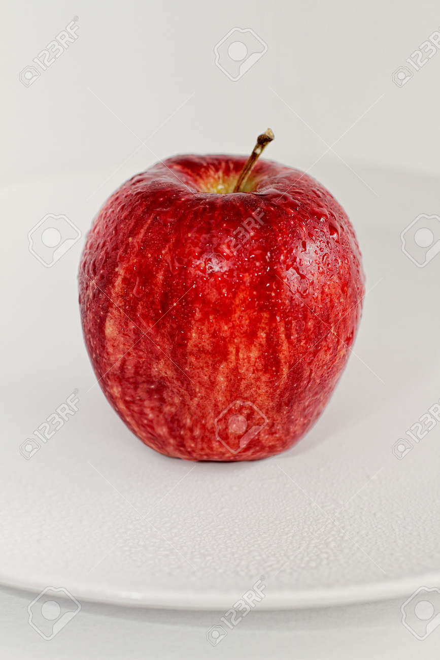 A Single Fresh Red Apple of a Plate Stock Photo - 7656116