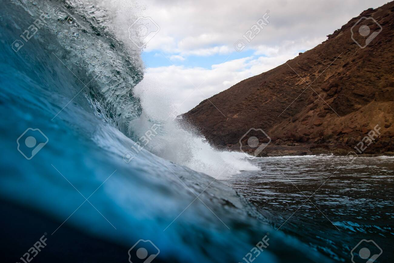 breaking wave with the tube and blue water with the clouds at the background - 139618275