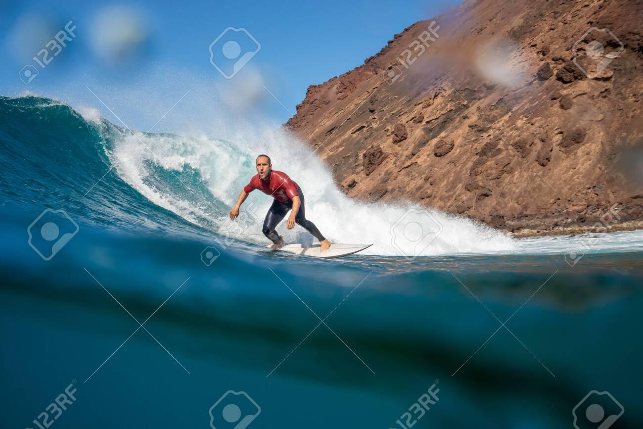 Surfer riding waves on the island of fuerteventura - 141805419