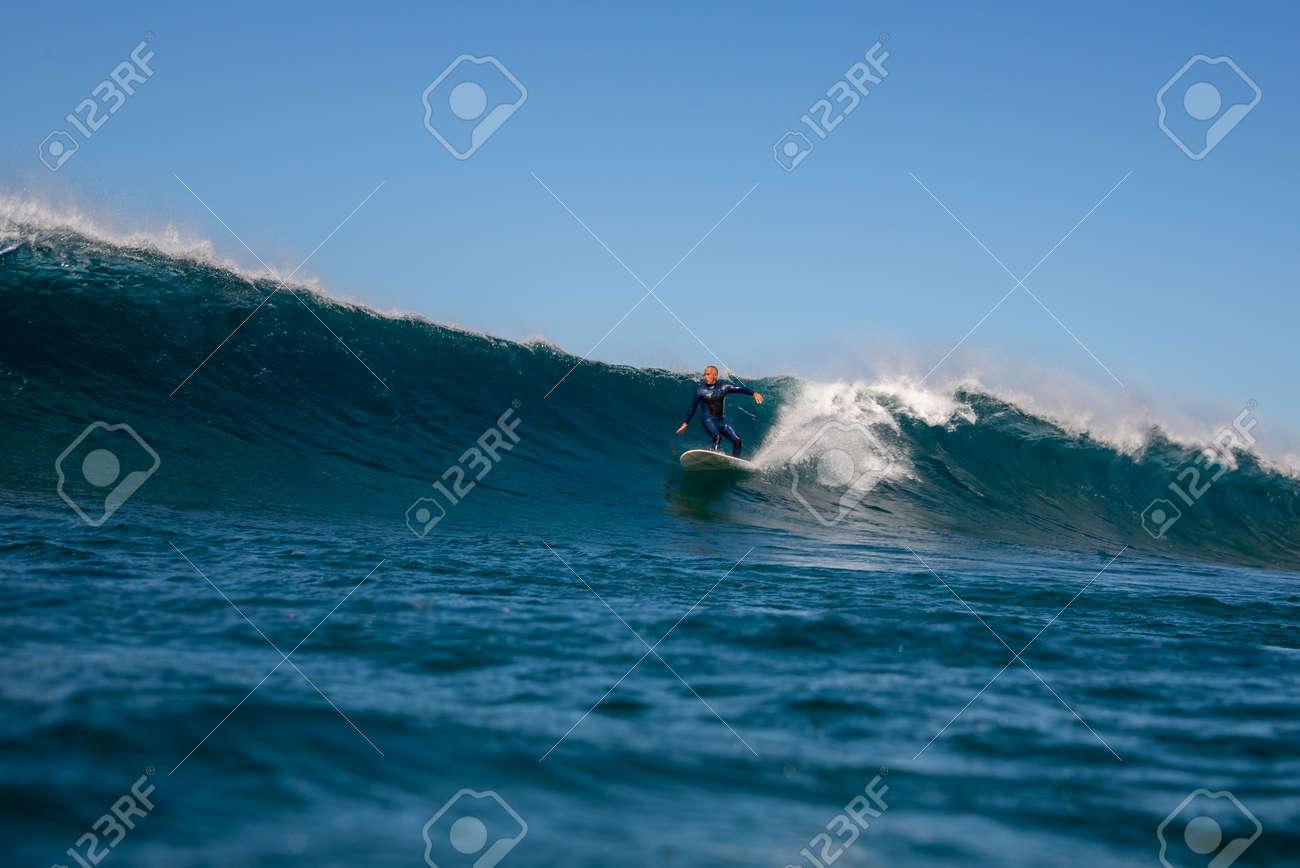 Surfer riding waves on the island of fuerteventura - 141805420