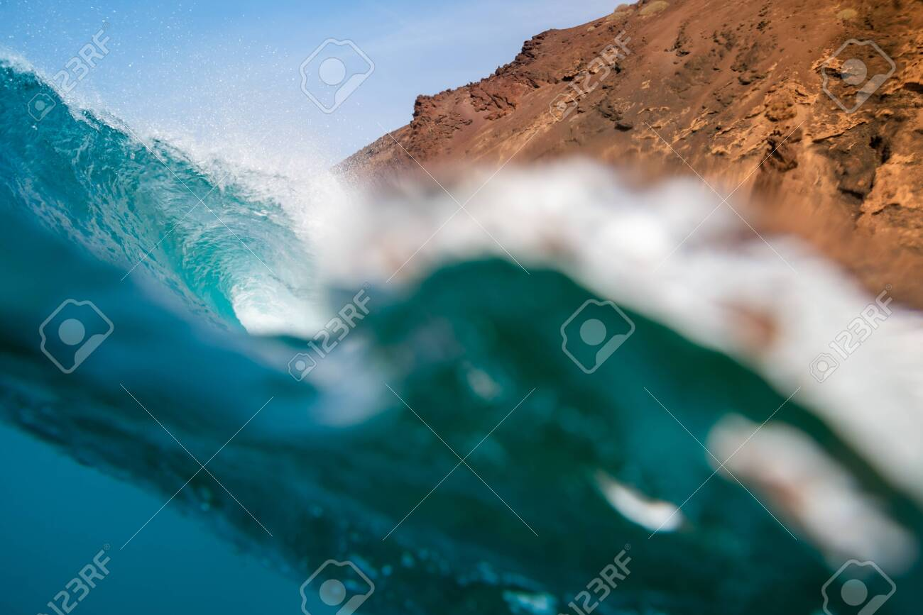 breaking wave with the tube and blue water with the clouds at the background - 141048149