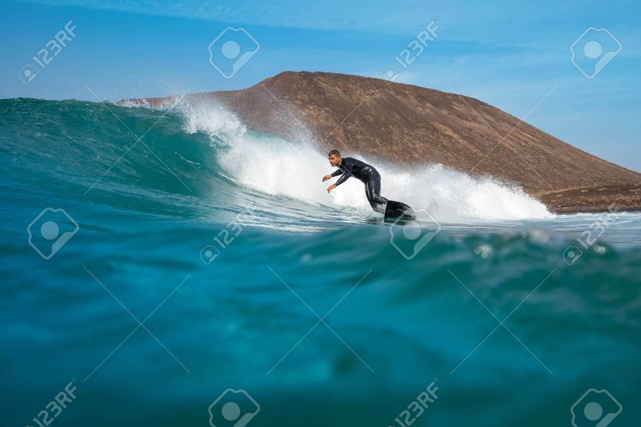 surfer riding waves on the island of fuerteventura - 143159816